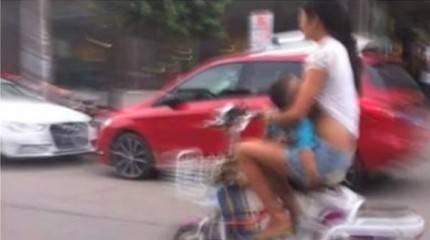 mamma che allatta in motorino