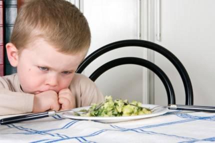 Bambino capriccioso di fronte a un piatto