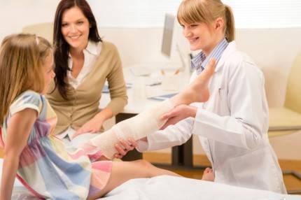 Dottore che controlla la gamba a una bambina