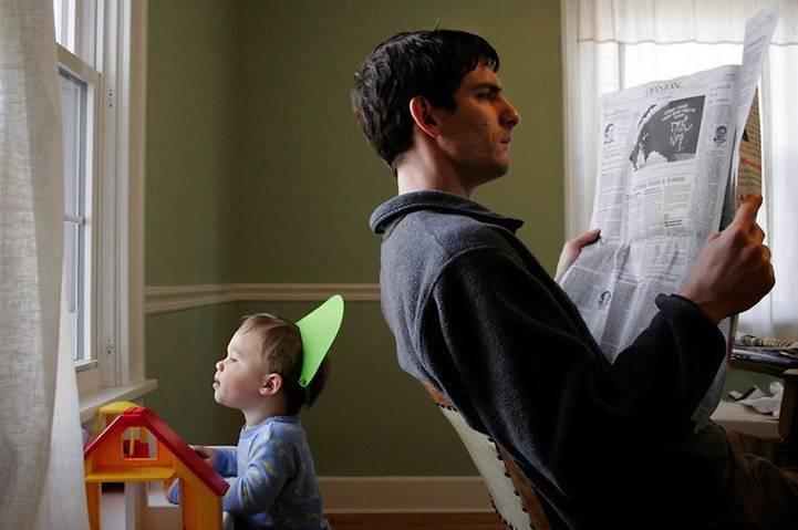padre e figlio di spalle, uno legge il giornale, l'altro guarda dalla finestra