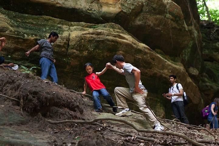 Padre sostiene figlio in un percorso in montagna
