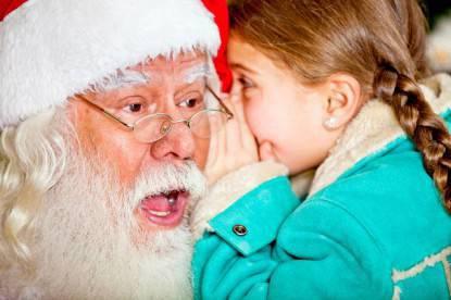 Bambina che racconta un segreto a Babbo Natale