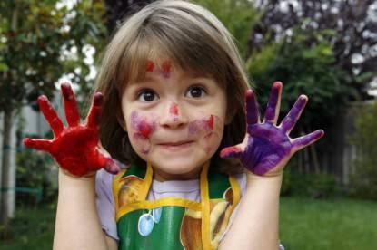 Una bambina mostra le sue mani colorate