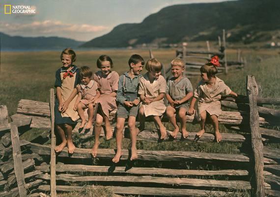 sette bambini seduti su una staccionata in paesaggio campestre