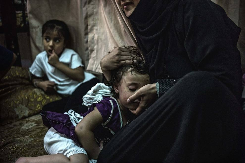 bambine con un adonna in situazione di miseria