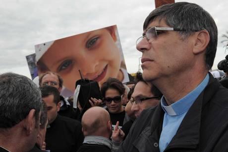 Foto di una vittima e il parroco