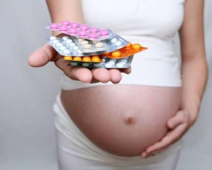 Una donna incinta tiene in mano delle pillole
