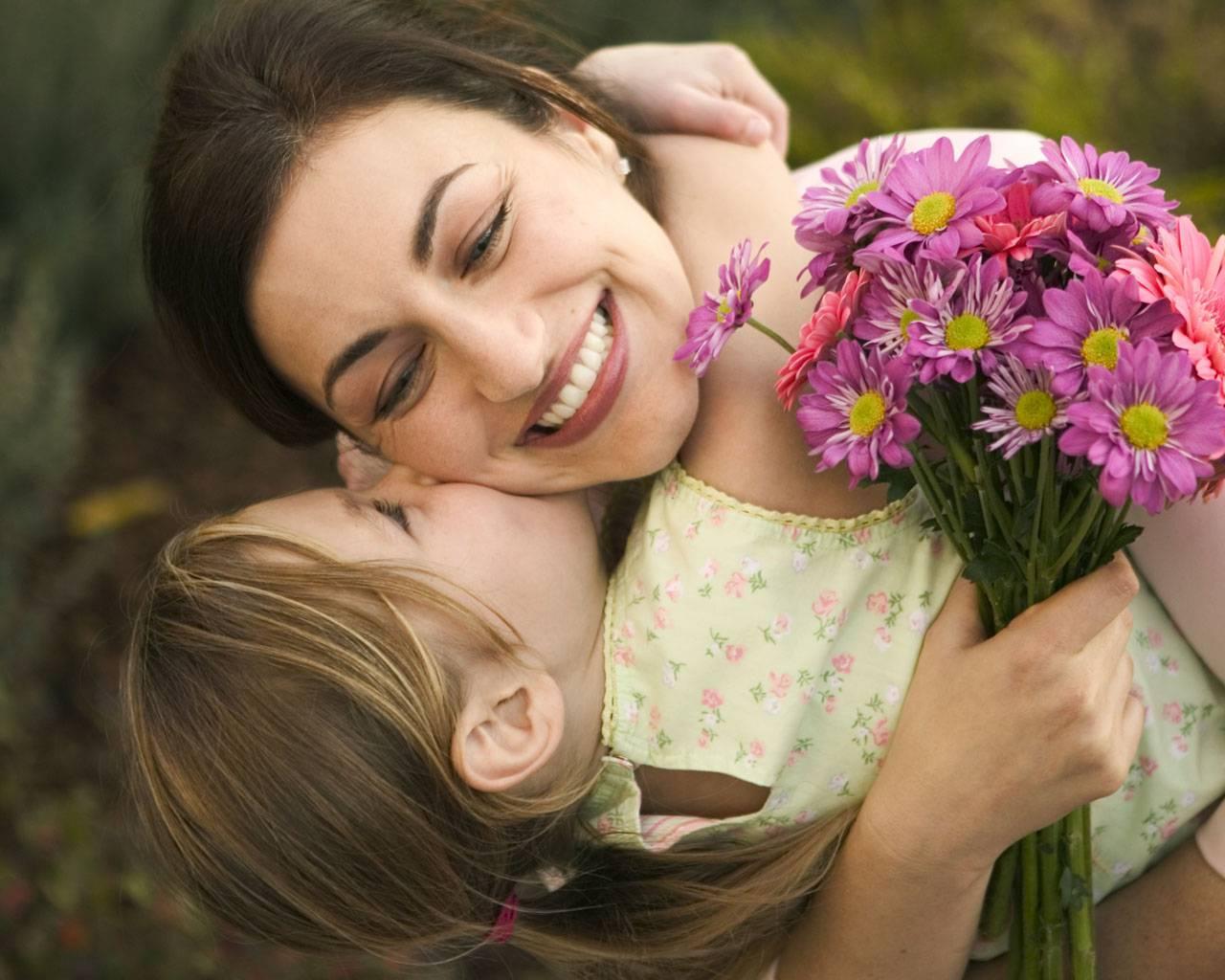 bambina che abbraccia mamma con mazzo di fiori