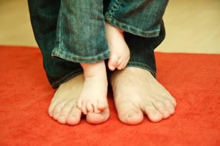 piedi grandi di un padre e piccoli figlio di pochi mesi