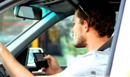 Un uomo scrive un sms mentre guida