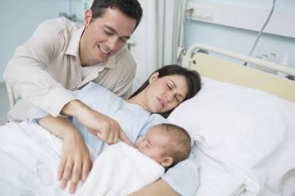 padre assiste la compagna che dorme ed il figlio appena nato