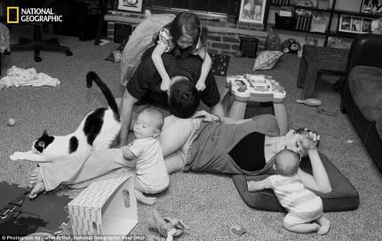 famiglia composta da madre padre ftre figli e gatto ripresa in bianco e nero distesi sul tappeto a giocare