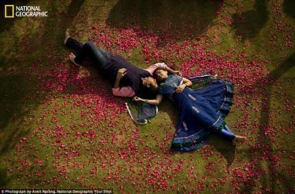 uomo e donna distesi su un prato attorniati di petali di rose