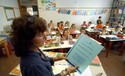 una donna insegnante in primo piano tiene registro in mano, dietro classe alunni seduti nei banchi