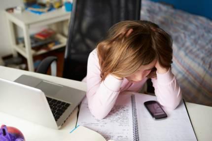 Una bambina sta facendo i compiti guardando anche il cellulare
