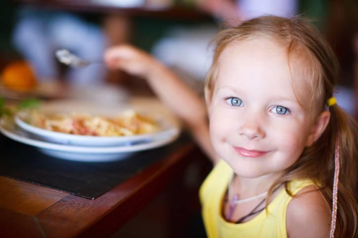 una bambina sta mangiando a tavola