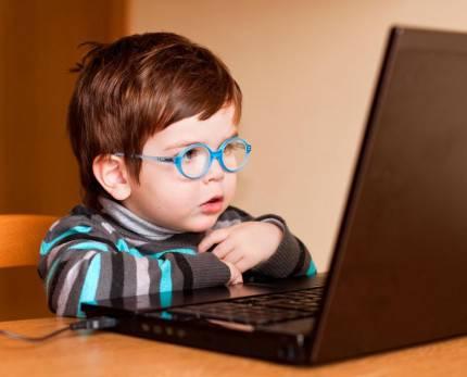 bambino piccolo circa due anni con occhiali davanti lo schermo di un personal computer