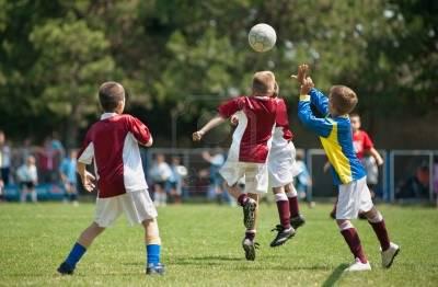 bambini che giocano a calcio e cercano di intercettare di testa il pallone