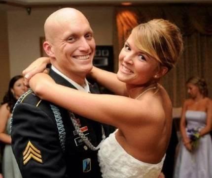 donna in abito da sposa e marito in abito militare che danzano per il loro matrimonio