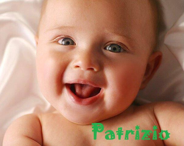 primo piano bambino di qualche mese con occhi verdi e capelli rossicci che ride