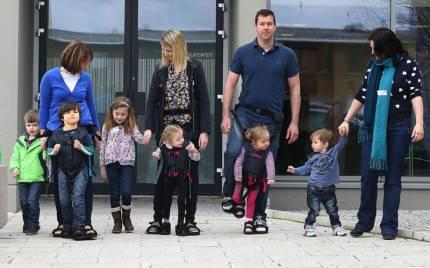 genitori che camminano insieme ai figli disabili sostenuti da una imbracatura che grazie al sostegno del loro corpo li fà camminare