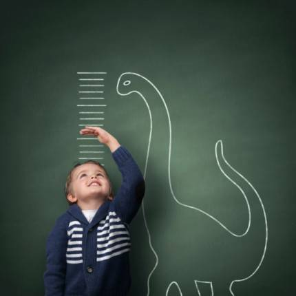 bambino che si misura con un dinosauro