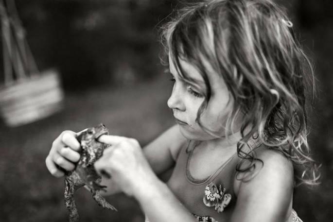 bambina gioca con rana