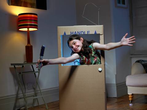 Girl playing in cardboard box TV