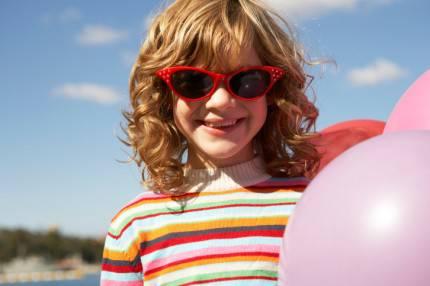 bambina sorridente che tiene in mano un pallone e indossa occhiali da sole