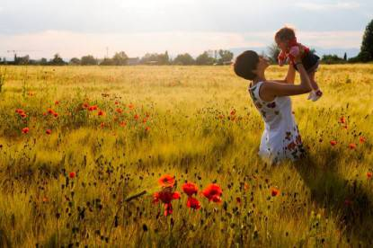 Woman smiling in a poppy field with her babby girl.