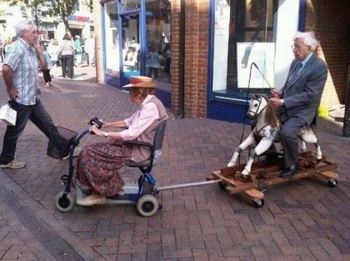 coppia anziana in bici e con cavallo dondolo