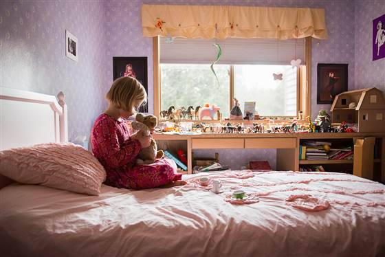 bambina sul letto col suo peluche