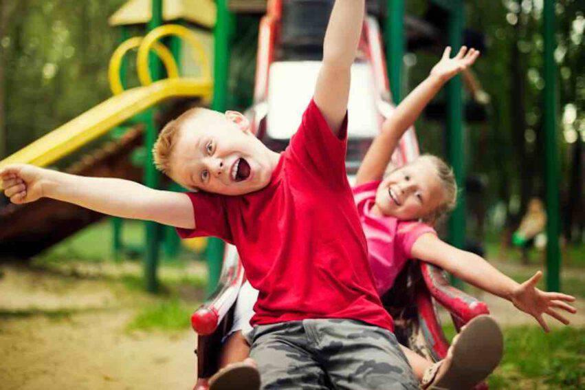bambini sullo scivolo al parco giochi