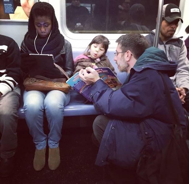 padre legge in metro alla figlia