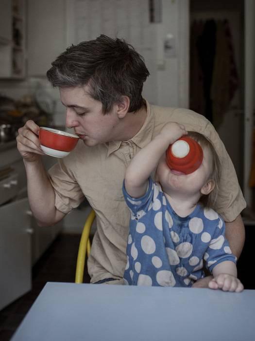 padre beve caffè con in braccio figlio