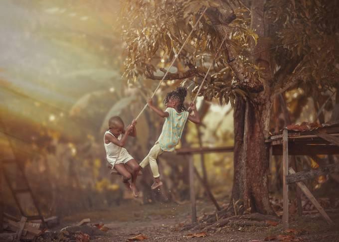 bimbi giocano altalena
