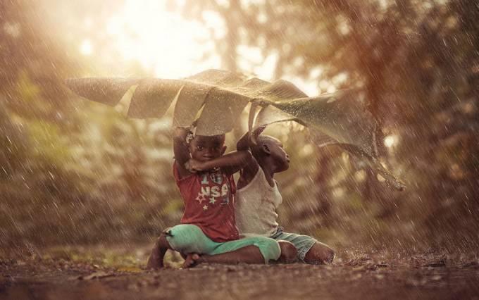 bambini si riparano dalla pioggia