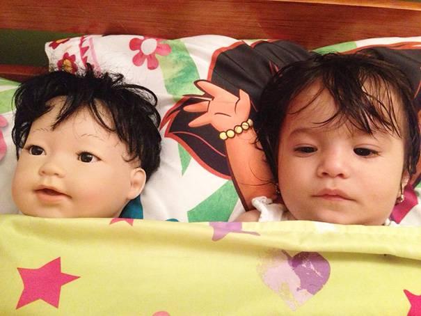 bambina e bambola a letto insieme