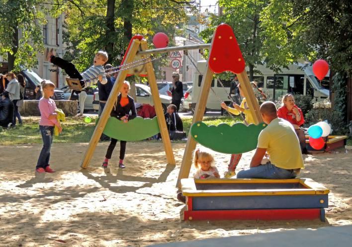 Un papà guarda i suoi bambini giocare al parco giochi