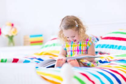 Little funny girl reading a book