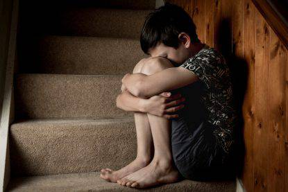Boy Crying Sitting on Stairs