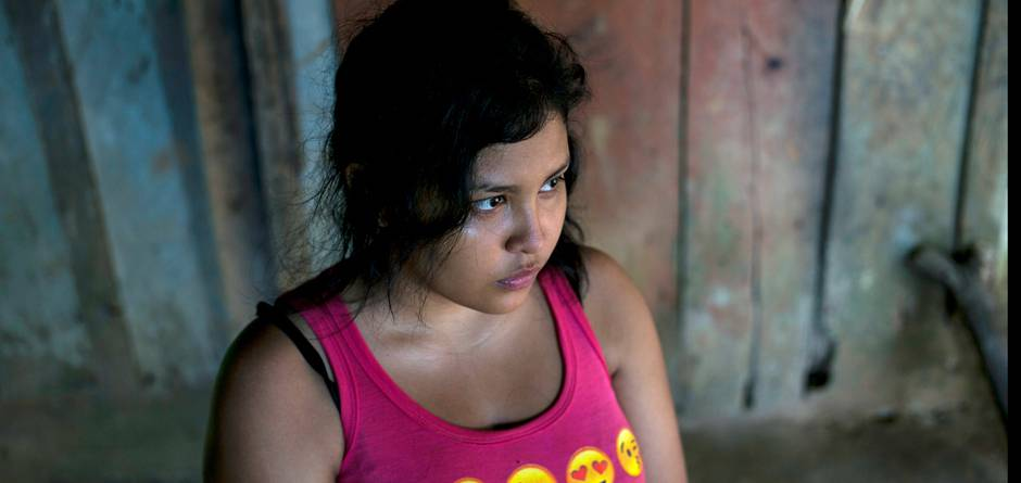 "Jackie, 17, Alexis' sister, in the family house in Omoa, Honduras on June 27th, 2016. She also wants to migrate, in spite of what happened to her brother: ""It terrifies me. It terrifies me just to think about it. But it also terrifies me to live this life, knowing there is no hope. At least I can take the risk, and have some hope."" Alexis, his mother and five siblings live in extreme poverty, in a wood and corrugated iron shack built on a slope that turns into mud every time it rains. Alexis, mother Mercedes, and the teenage children work odd jobs when they can find them harvesting cocoa pods or chiles. Two older siblings who work and live in nearby towns help out as much as they can. Mercedes said ""Alexis had left because of poverty. He told me he was going so he could help me and all the children I have. He wanted to study."" At the age 16, Alexis and a cousin packed their meager belongings and hit the road, hoping to escape the bitter poverty in which they grew up in Honduras. Like hundreds of thousands of others from Central America, they hoped to make it to the United States. But for Alexis, the journey ended in Mexico, when he fell off a freight train and lost his right leg - not an uncommon injury on the notorious route. Now, he is back home - a wood and corrugated iron shack built on a slope that turns into mud every time it rains. His mother and his teenage siblings work odd jobs when they can find them, harvesting chilies, taking care of other people's children or helping out in food stalls. Getting to the United States, was about more than just ""an American dream,"" says Alexis. ""It's about getting out of the country, which has so much poverty. I wanted to get there and work and help my brothers and my mother."" Alexis sometimes joins a local UNICEF-supported outreach group to tell other young people about the dangers of the journey. But he's convinced his own siblings will eventually try to head north. ""For the same reason I left here, my brothers and"
