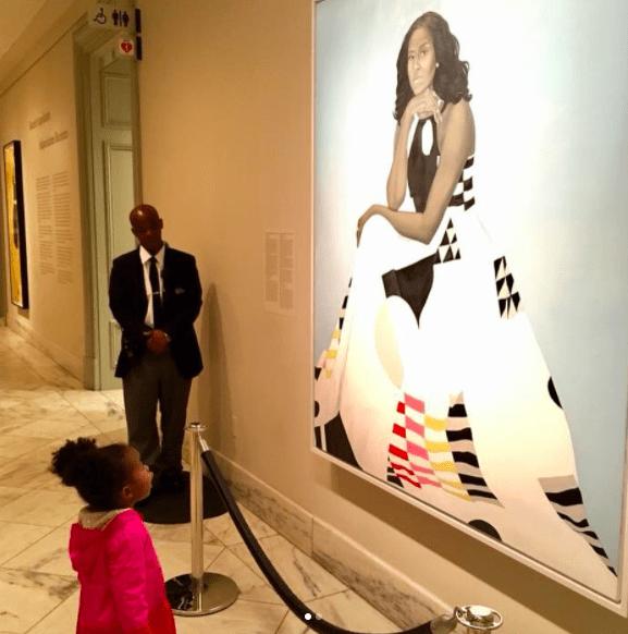 bambina guarda estasiata quadro michelle obama