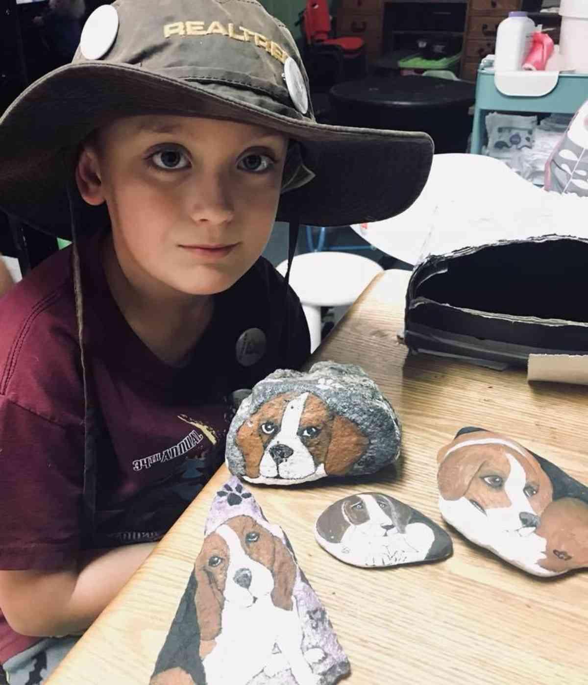 bambino dipinge pietre