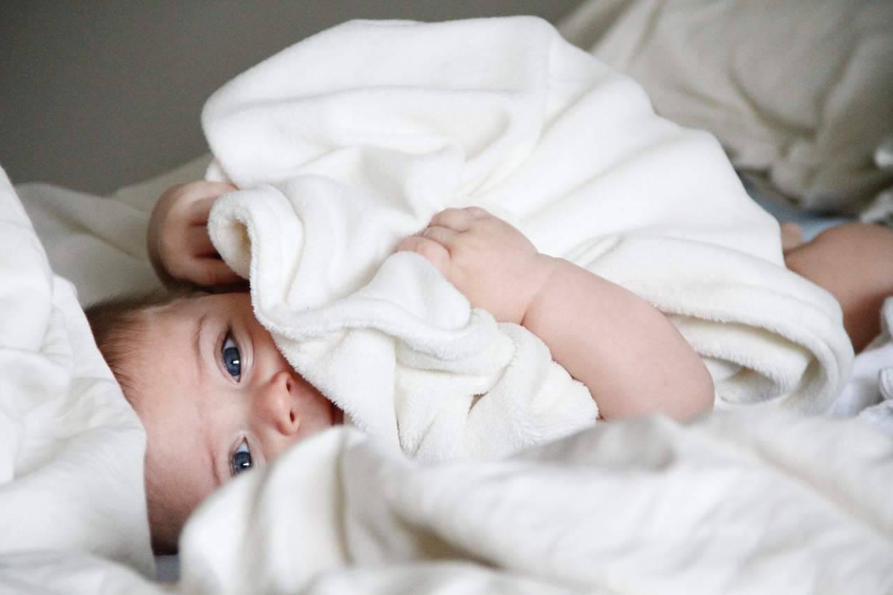 Bimbo tra le coperte (fonte unsplash)