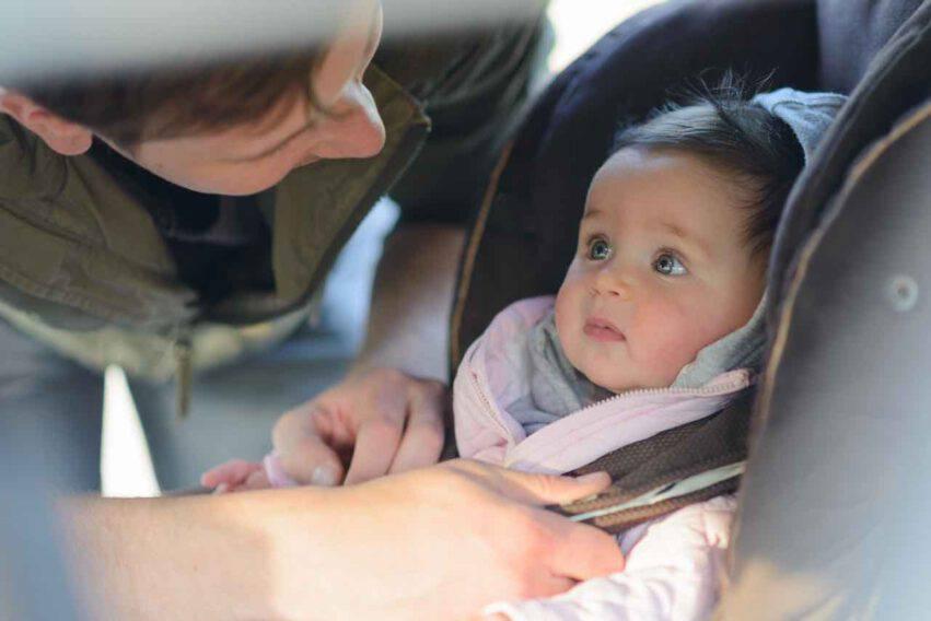 papà lega bambina al seggiolino in auto