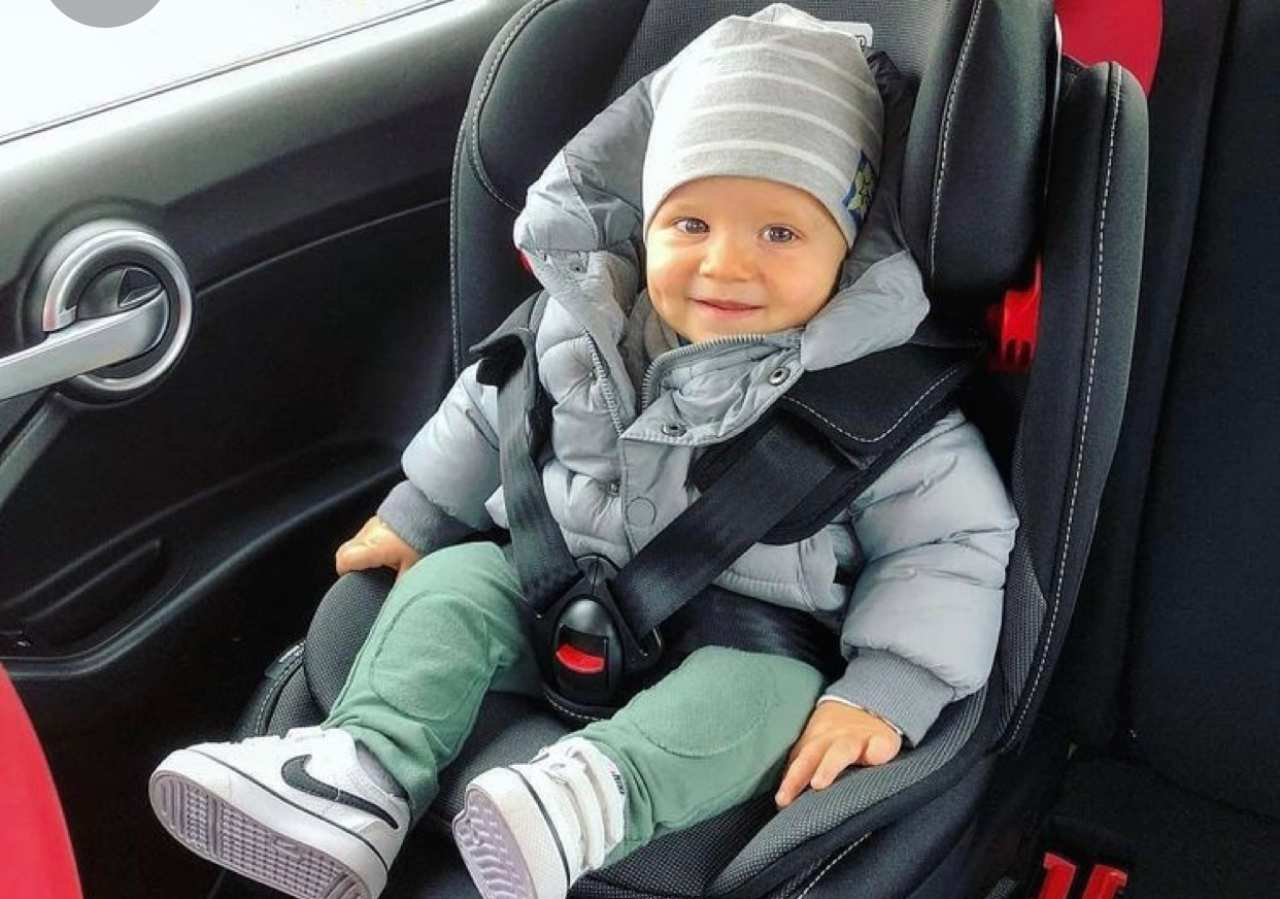bambino con giubbotto in auto sul seggiolino