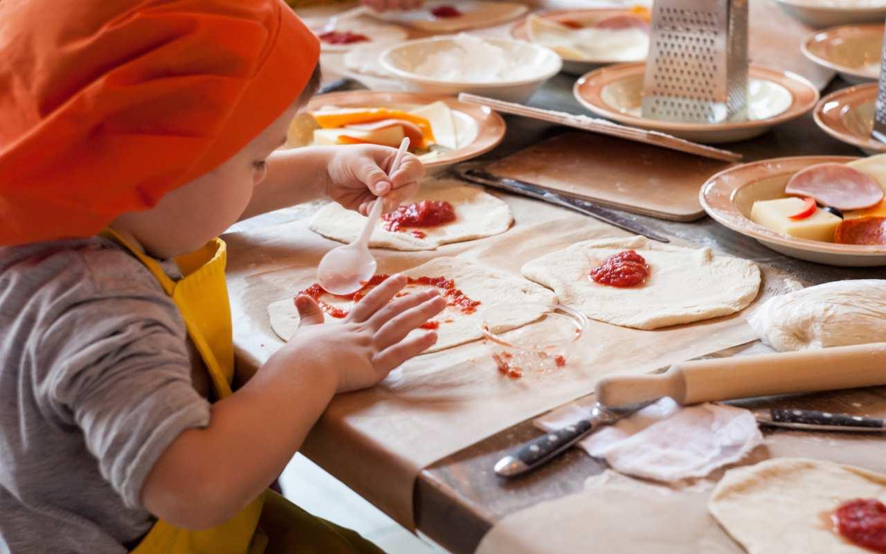 Bambino che prepara la pizza