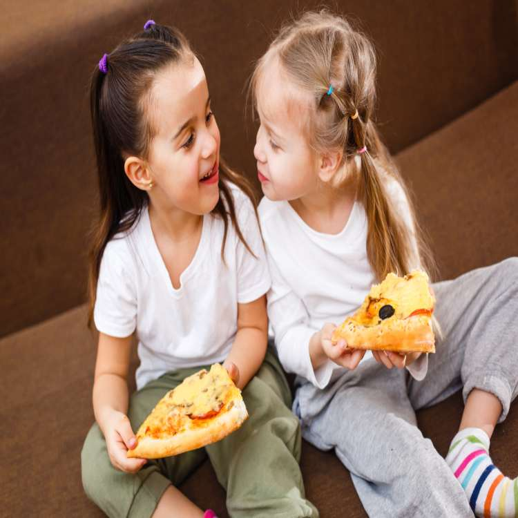 Bambine che mangiano la pizza